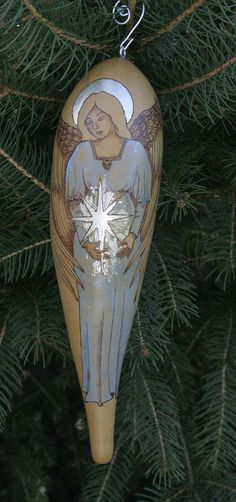"This is a real, organically grown banana gourd that has been dried ( it will last for many years and made into an ornament.  This ""Angel with Star"" has been freehand drawn, and pyroengraved ( woodburned ) & painted, with gold leaf halo, and silver leaf star. The color of the dress is oil paint glazed lightly over the woodburning & comes with a hand made wire hook."