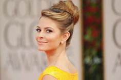 """While this might seem like an ordinary high bun, Maria Menounos' side-swept bangs (which create a """"swooping"""" effect) give this classic hairstyle a fun twist."""
