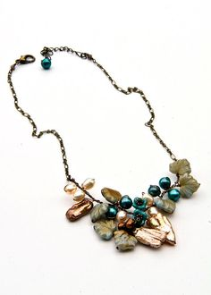 Brown and teal beaded necklace is a beautiful bouquet of freshwater pearls and leaves along with tiny flowers. There is a lovely organic