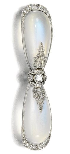MOONSTONE AND DIAMOND BROOCH, CARTIER, CIRCA 1905.  Designed as a bow set with two pear-shaped cabochon moonstones accented with circular-cut and rose diamonds, signed Cartier Paris and numbered, French assay marks.