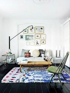 parquet chene massif noir et tapis coloré dans le salon murs blancs