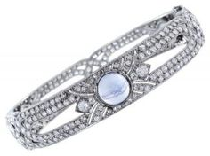 Platinum Art Deco Bangle Bracelet Consisting Of Approximately 10.00 Carats Total Weight Of Old European Cut Diamonds, Set With 3 Round Cabochon Moonstones Approximately 8.50 Mm In Diameter And Accented With Engraving And Millgrain Edges.