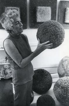 Claire Zeisler (American fibre artist) and her giant pom poms, 1972.