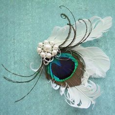 Brides.com: All Things Peacock. Then add a subtle hint of peacock flavor to your wedding day look with a stylish feathered headpiece.  Pearled Peacock fascinator, $32, Peacockpixys.etsy.com