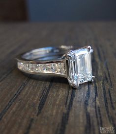 Classic emerald cut diamond engagement ring with channel set square cut diamond sides. Estate from Doyle & Doyle.