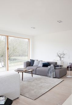 Modern and minimalist living room in shades of grey with a large window front.