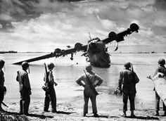 histored - US troops examine a wrecked Japanese seaplane at Makin Atoll (1943)