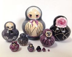 MeganMissfit: This listing is for a set of one of a kind Russian nesting dolls (Matryoshka) painted by hand with acrylic paints by me, the artist. A creepy yet beautiful spin on the traditionally painted dolls, this piece was inspired by dark fairy tales, with motifs of roses, thorns, dead trees, ribbons and skulls. The dolls were painted with a mix of greys, blacks, whites, soft purples, and pinks.