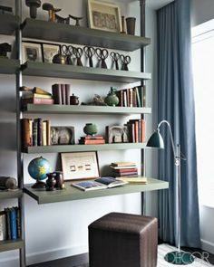 Hillary Swank's home-A floor lamp from Design Within Reach stands next to custom-made metal-and-wood shelving; the ottoman is by Calvin Klein Home.