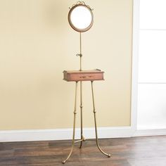 "Antique Victorian Shaving Stand This shaving stand with a beveled mirror is a rare find! Three brass legs hold up a drawer adorned with pierced brass detail and an adjustable, framed mirror. A unique and functional find that will add historical charm. Drawer measures 2""Hx11""Wx6""D (60""Hx14 ""Wx14""D"