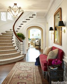 A plush custom-made settee lends an inviting tone to the entry, paired with a vintage Oushak rug.    - HouseBeautiful.com