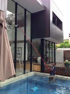 Window cleaners at work in a pool to access this extremely high window. With no area to use a ladder the only safe option in this situation is to use our water fed pole and pure water system. Our Brisbane window cleaning team deliver perfect results every time.