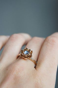 Moonstone engagement ring is hand-sculpted from solid 14K gold sheet and features several layers of lotus flower petals. Flower engagement ring is adorned with natural 4,5 mm blue moonstone cabochon, it is clear as a real water drop. You can choose yellow, rose or red gold color during