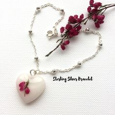 Delicate Handmade Item  * Material: Real Heather Heart Small Pendant in Resin attached to a delicate Genuine 925 sterling silver satellite bracelet. It is made with sterling silver satellite chain and closes with a sterling silver clasp.    * Size:  *The Flower Heart Pendant is 1.8cm at it's widest part.    *The Sterling Silver Bracelet is 7.2inches Long  (18.5cm)     The Exquisite and Stunning combination of Genuine Sterling Silver Bracelet and Real Flower Heart Pendant Will Make You Stand…