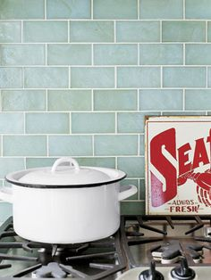 Sea green glass tiles establish a beachy theme in this waterfront kitchen overlooking Long Island's Peconic Bay. The result is fresh and inviting. - CountryLiving.com