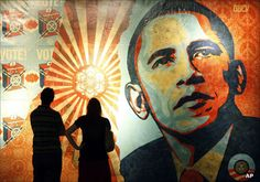 A couple standing in front of Shepard Fairey's Obama Hope mural