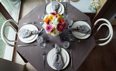Indoor dinner for four. White plates, gerberas bouquet.