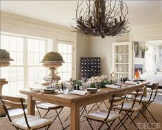 Reclaimed tables, nest chandelier, topiaries, folding chairs -   Elle Decor