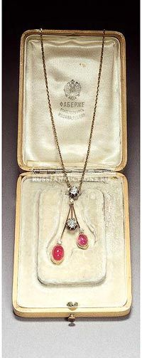 A ruby and diamond pendant necklace by Faberge, circa 1900. In the form of three drops, mounted with two cabochon rubies and five diamonds.