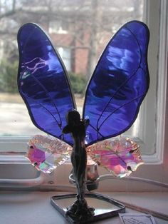 """This stained glass and German Crystal fairy lamp comes with a detachable light and takes either a 5 or 7 watt bulb. It is very beautiful at night if you use it as a night light and the light makes the bottom crystal wings sparkle. This lamp comes in many colors so please specify what color you want. It is approx. 9-10"""" tall and it cost $55.00 each."""