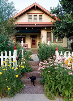 A bungalow front garden with picket fence and a profusion of daylilies, and purple coneflower shows great curb appeal. Bungalow Landscaping, Bungalow Exterior, Bungalow Homes, Craftsman Style Homes, Craftsman Bungalows, Exterior House Colors, Landscaping Ideas, Exterior Design, Craftsman Exterior