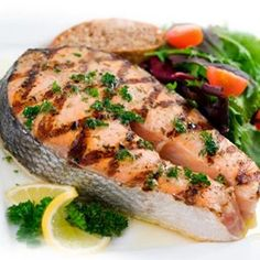 Poached salmon steak with vegetables and dry white wine..