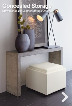 Storage ottoman under a small desk for a small guest room