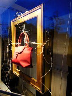 Window Display - French purse tied with twine onto gold frame in r.h. ballard shop window.