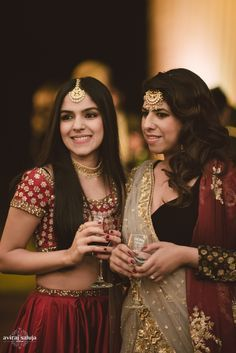 Sisters of the Bride - Maroon and Gold Outfits | WedMeGood | Bride in a Gold and Beige Net Saree and a Maroon Dupatta and the Sister of the Bride in a Maroon and Gold Lehenga . Gold Maang Tikka #wedmegood #sister #bridal #choli #indian