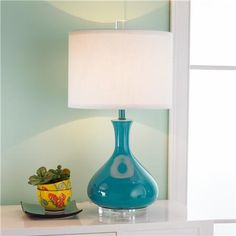 "The smooth glossy finish is accented with a sleek clear acrylic base and finial then topped with a white fabric drum shade for ultimate versatility wherever you need a pop of satisfying color. Select from vibrant hand picked tones of; Turquoise teal, Orange coral, apple Green, Navy blue, Red rose, and lemon Yellow, or calm neutrals like spa Blue, dove Gray, chocolate Brown, sandy Beige, classic Black and studio White. 60 watts. Made in the USA. (25""H x 14""W) $259"