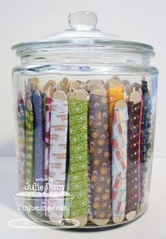 DIY Organization - Store ribbon in inexpensive glass containers. Each piece of ribbon is wrapped around a wide popsicle stick.Frugal Friday: 25 DIY Organization Ideas - One Good Thing by JilleeClever idea for ribbon storage DIY. I'm just going to do Ribbon Organization, Ribbon Storage, Sewing Room Organization, Craft Room Storage, Diy Storage, Organizing Ideas, Storage Ideas, Fabric Storage, Craft Rooms