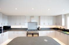 Stunning white kitchen with slate worktops either side of a modern oven and hob.