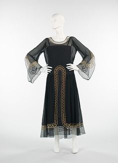 Embroidered black silk chiffon evening dress with black slip, designed by Jeanne Lanvin, French, 1925. The basic silhouette on this Lanvin dress evokes religious robes worn by monks while the sheer textile makes it elegant and refined, trademarks of her work. In addition, the Greek key motif shows her knowledge and interest in incorporating classical design motifs in her fashions.