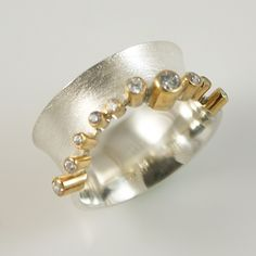 Martin Młynarczyk | Very elegant, wide ring with cubic zirconia framed on one edge and gilded.