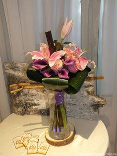 Bouquet de marié structuré de bamboos bien agencé de Lys roses, de Roses roses, de Lys Calla violets et de Feuilles d'aspidistras.