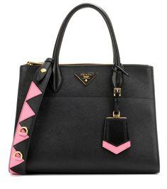 Prada - Sac en cuir Paradigme - Prada signe ce sac noir en cuir saffiano signature et l'illumine de détails dorés et de finitions roses, assorties à l'intérieur spacieux. Ce modèle à l'élégance intemporelle arbore naturellement le fameux empiècement triangulaire à lettres métallisées. seen @ www.mytheresa.com