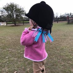 At a horse show, a very young equestrian, wearing her Bowdangles Horse Show Bows, adjusts her helmet strap before her leadline class.