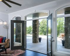 Open glass doors provide uninterrupted views to the rear patio. The Monarch Manor house plan 5040. #WeDesignDreams
