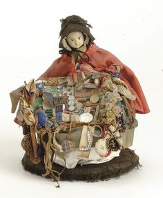 """Germany, mid 19th century, young lady peddler with finely molded papier mache shoulder head with molded black hair and attached wig in back, painted features with blue eyes, wearing original costume with red cotton cape and black hat, carrying original basket with wares, on a velvet base, 8"""" t."""