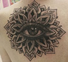 Grey-ink mandala flower with eye tattoo on back