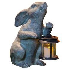"""Rabbit statue carrying a solar lantern.  Product: LanternConstruction Material: Resin and glassColor: Stone and brownFeatures: Solar powered lightDimensions: 19"""" H x 9.5"""" W x 14"""" D"""
