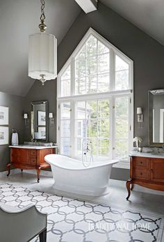 The master bath features his-and-hers vanities made from chests converted into sinks. The geometric floor pattern was a custom design and serves as a bold focal point. Corey Damen Jenkins & Associates | Michigan Design Center