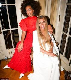 Besties: Her sister Solange stood out in a pretty red dress and white pointy heels