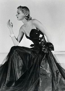 """""""September 1937. The new note of fall evening gowns is the revealing style of tight, form fitting gowns. The tight corsetlet bodice of this stunning Chanel gown, which ties in bows at the hips and hangs down over the full panels of black silk net. The gown itself is on black taffeta, too. Notice the daringly revealing neckline, flesh-colored shoulder straps and bouffant skirt."""""""