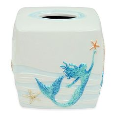 Evoke the essence of the deep, serene sea into your bathroom with the Bacova Sea Splash Boutique Tissue Box Cover. Adorned with hand painted mermaids, sea creatures, and coral, this resplendent cover will infuse an aura of tranquility and beauty.