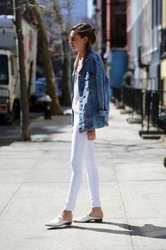 Love this We Wore What outfit: white skinny jeans, a denim jacket, and flat mules