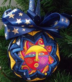 """Celestial Dreams  This 3"""" handmade quilted ornament is made with the Laurel Burch Celestial Dreams fabric with bright colors. I layered yellow and blue glitter fabric to add that pop to the ornament. This ornament would look charming in your favorite bowl or basket or as a decoration in a room. It will make a great Christmas tree decoration! It makes a great gift for family, friends, or teachers.  These ornaments are made by hand so no two are exactly alike.  This ornament comes gift boxed…"""
