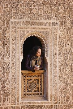 a woman in a Ben Yousef Madrasa window , Marrakesh , it was founded by a Marinid Sultan Abu Al-Hasan Ben Yousef 1346 Ac