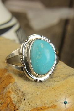 This is a beautiful handmade Navajo sterling silver turquoise ring. This ring is centered with a unique quality turquoise stone which is surrounded by a time consuming hand filed silver work border. The face of the ring is supported on a sturdy sterling silver band. The ring is Sterling Silver and made by Native artist Edward Secatero a member of the Navajo Tribe. Size 6.5. The piece is 1/2″ at its widest point.