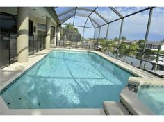 812 Eagle Ln, Apollo Beach, FL 33572 — Waterfront living at its finest! Stunning 4 bedroom, 4 bath home with a bonus room situated on large fenced lot with 100 ft of water frontage. Double entry doors open to a spacious great room with vaulted ceilings featuring grandiose tropical ceiling fans. Sliding glass doors tuck away to extend the indoor living space out onto the covered patio. A sparkling heated swimming pool and spa, housed under a newly screened enclosure, add to the ambiance to…